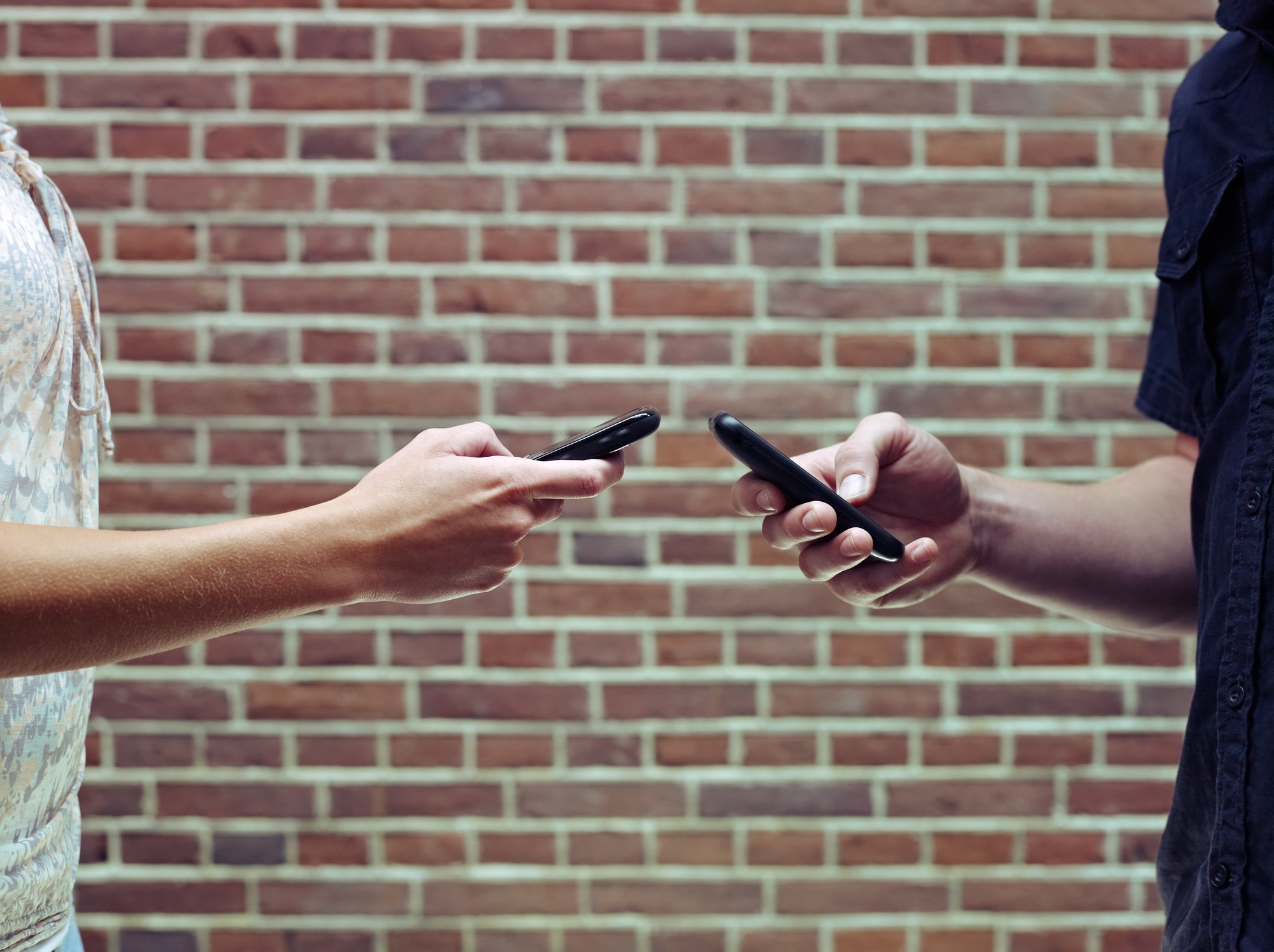Man And Woman Using Cellphones To Share Files And Contacts